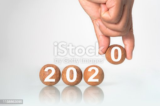 istock Hand putting on Wooden ball 1158863595