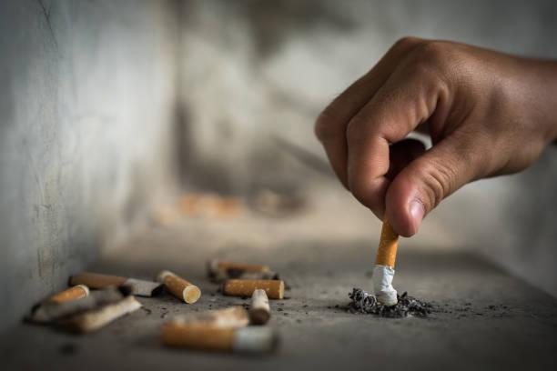 hand putting out a cigarette,cigarette butt - cicca sigaretta foto e immagini stock