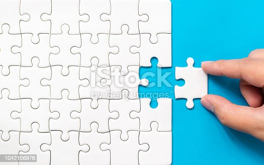 istock Hand putting piece of white jigsaw puzzle on blue background. Team business success partnership or teamwork. 1042156976