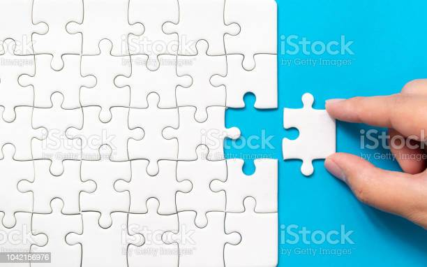 Hand putting piece of white jigsaw puzzle on blue background team picture id1042156976?b=1&k=6&m=1042156976&s=612x612&h=qrhpuhqqbxmiy7ltxyurtryty4etypeycjwqoravdhi=
