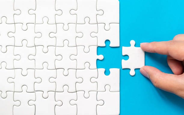 Hand putting piece of white jigsaw puzzle on blue background. Team business success partnership or teamwork. stock photo