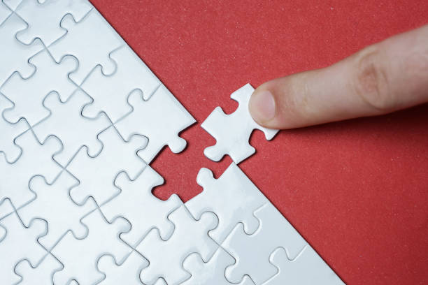 Hand putting piece of white jigsaw puzzle on red background. Team business success partnership or teamwork. stock photo