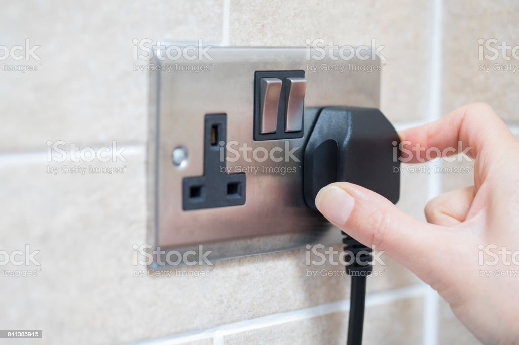 Hand Putting Plug Into Electricity Socket royalty-free stock photo