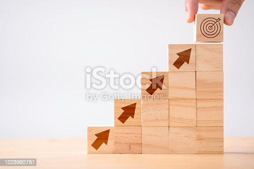 Hand putting print screen dart and target board wooden cube on up arrows. Target of investment and business concept.