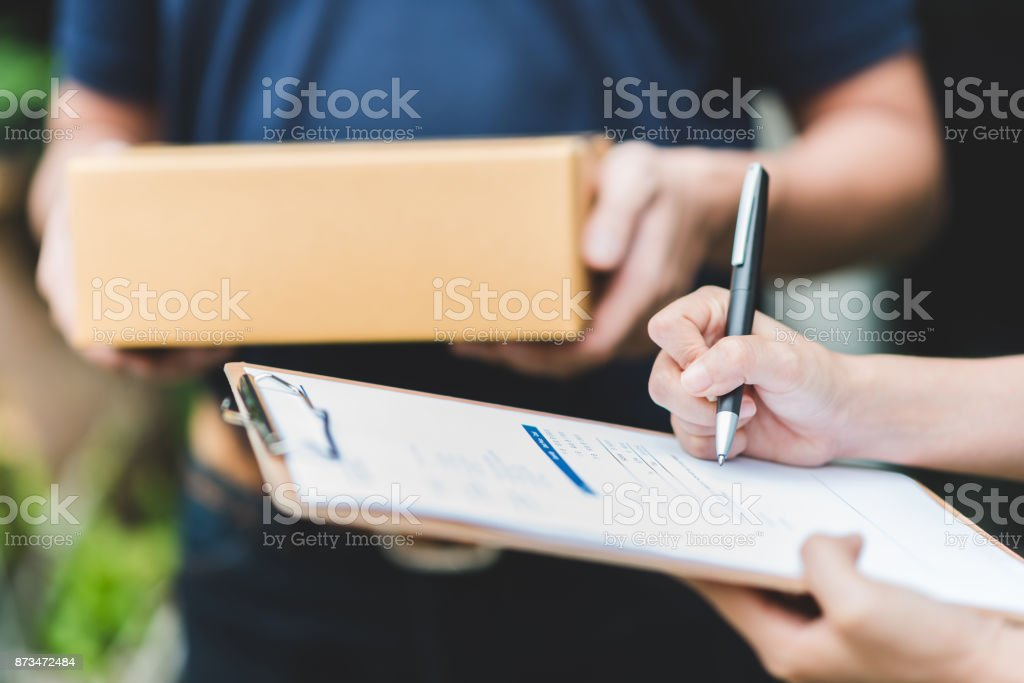 Hand putting signature in clipboard to receive package from delivery man stock photo