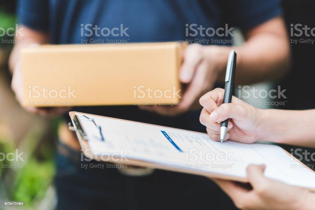 Poner firma en portapapeles para recibir paquete de repartidor de la mano - foto de stock