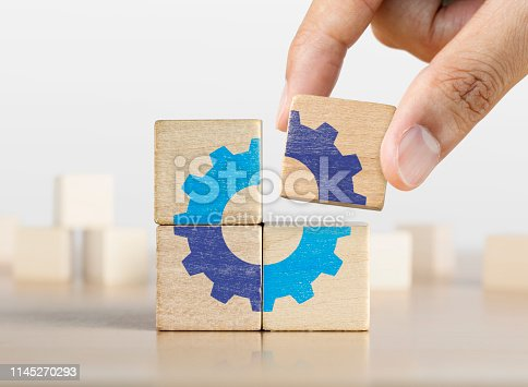 istock Hand putting the last piece of wooden blocks with the gear icon. Team work, unity, partnership or integration concept. 1145270293