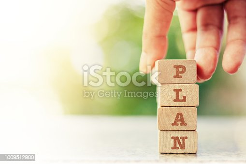 istock Hand putting the wooden toy with word PLAN for business plan concept 1009512900