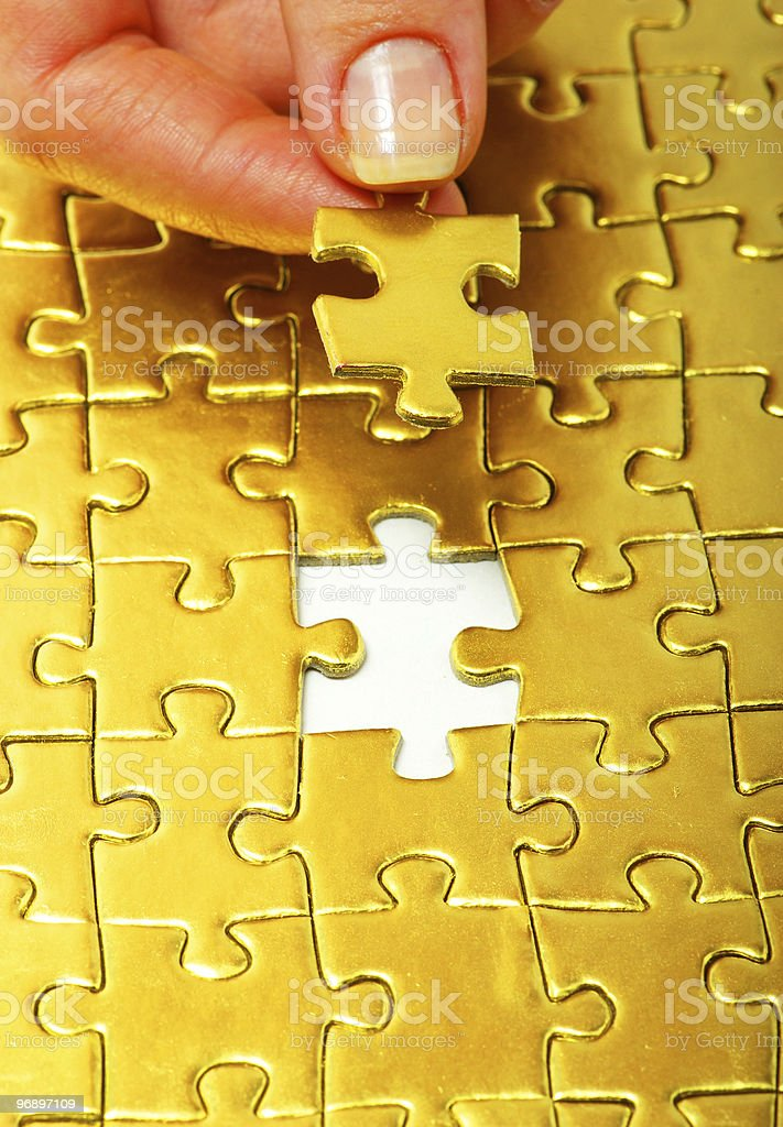 Hand putting together gold puzzle pieces royalty-free stock photo