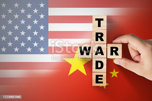 Hand putting trade war wording on USA and China flag.It is symbol of tariff trade war tax barrier between United States of America and China.-Image.
