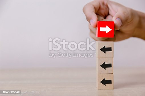 istock Hand putting wood cube block on top vertical red wooden blocks with white arrows facing opposite to the black arrows. With different concepts to other people. Going for success. 1048835546