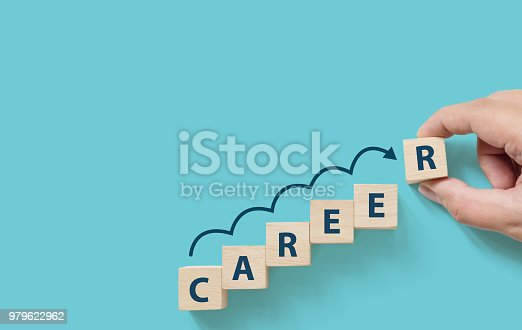 Hand putting wooden cube block on blue background with word CAREER and copy space for your text. Business career planning growth to success concept