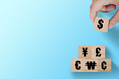 Hand putting wooden cube of US dollar sign to Yuan  Yen Euro and Pound sterling sign.US dollar is main and popular currency of exchange in the world.Investment and saving concept.