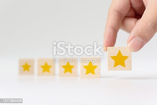 1133580311 istock photo Hand putting wooden cube with five star shape on white background. The best excellent business services rating customer experience concept 1217364428