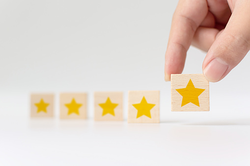 917079212 istock photo Hand putting wooden cube with five star shape on white background. The best excellent business services rating customer experience concept 1217364428