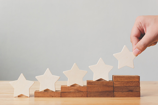 917079212 istock photo Hand putting wooden five star shape on table. The best excellent business services rating customer experience concept 1029077200