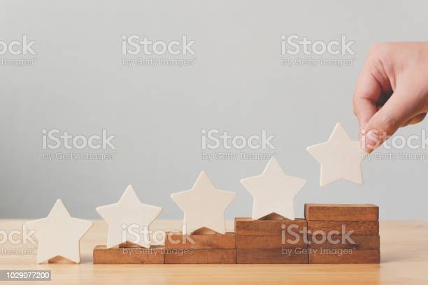 Hand putting wooden five star shape on table the best excellent picture id1029077200?b=1&k=6&m=1029077200&s=612x612&h=zjfohdvdwx5rnlwkwq616pesycnbv0apy3b5rszxuy0=