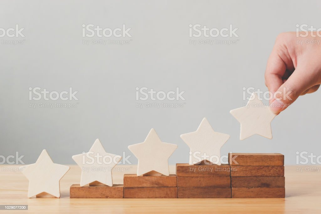 Hand putting wooden five star shape on table. The best excellent business services rating customer experience concept stock photo