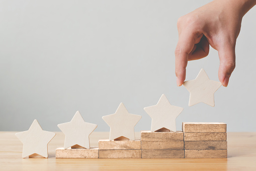 917079212 istock photo Hand putting wooden five star shape on table. The best excellent business services rating customer experience concept 1133580311