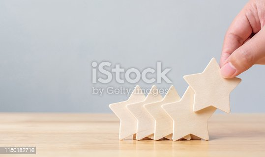 1133580311 istock photo Hand putting wooden five star shape on table. The best excellent business services rating customer experience concept 1150182716