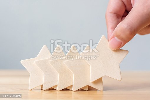 1133580311 istock photo Hand putting wooden five star shape on table. The best excellent business services rating customer experience concept 1171703425
