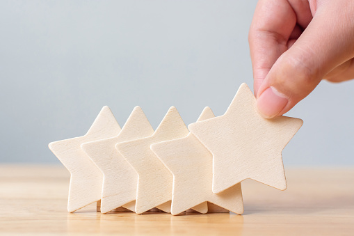 917079212 istock photo Hand putting wooden five star shape on table. The best excellent business services rating customer experience concept 1171703425