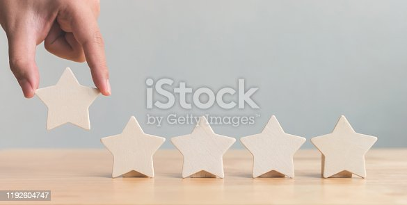 1133580311 istock photo Hand putting wooden five star shape on table. The best excellent business services rating customer experience concept 1192604747