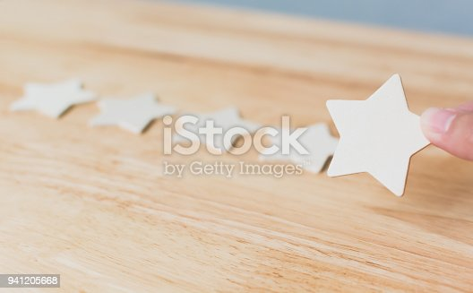 1133580311 istock photo Hand putting wooden five star shape on table. The best excellent business services rating customer experience concept 941205668