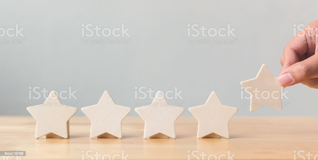 Hand putting wooden five star shape on table. The best excellent...