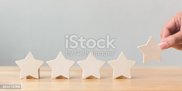 istock Hand putting wooden five star shape on table. The best excellent business services rating customer experience concept 944415288
