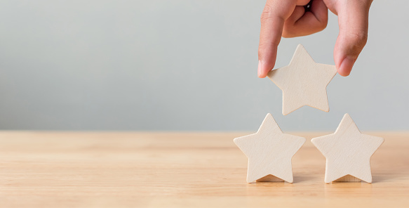 917079212 istock photo Hand putting wooden five star shape on table. The best excellent business services rating customer experience concept 961637964