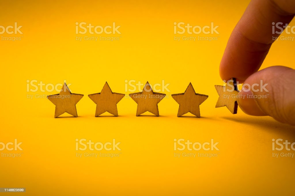 Hand putting wooden five star shape on yellow background. The best...
