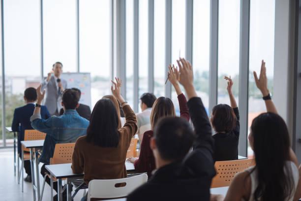 hand raised for vote and asking at conference seminar meeting room - formazione degli adulti foto e immagini stock