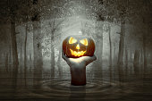 Hand raised from the water and holding Jack-o-Lantern on the haunted forest. Halloween concept