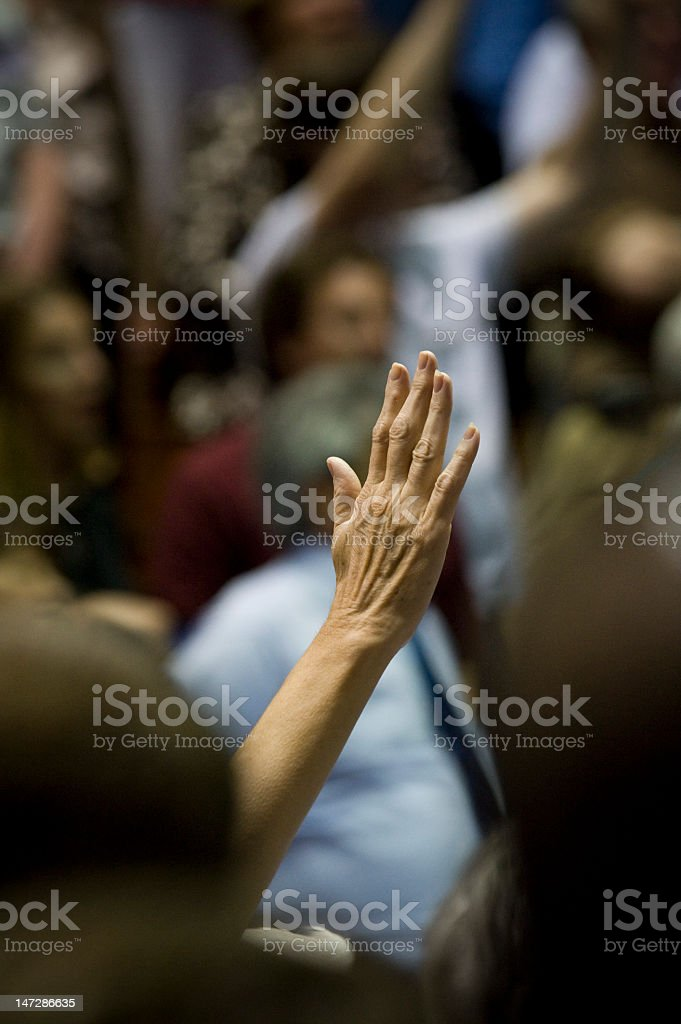 Hand raised in middle of large crowd royalty-free stock photo