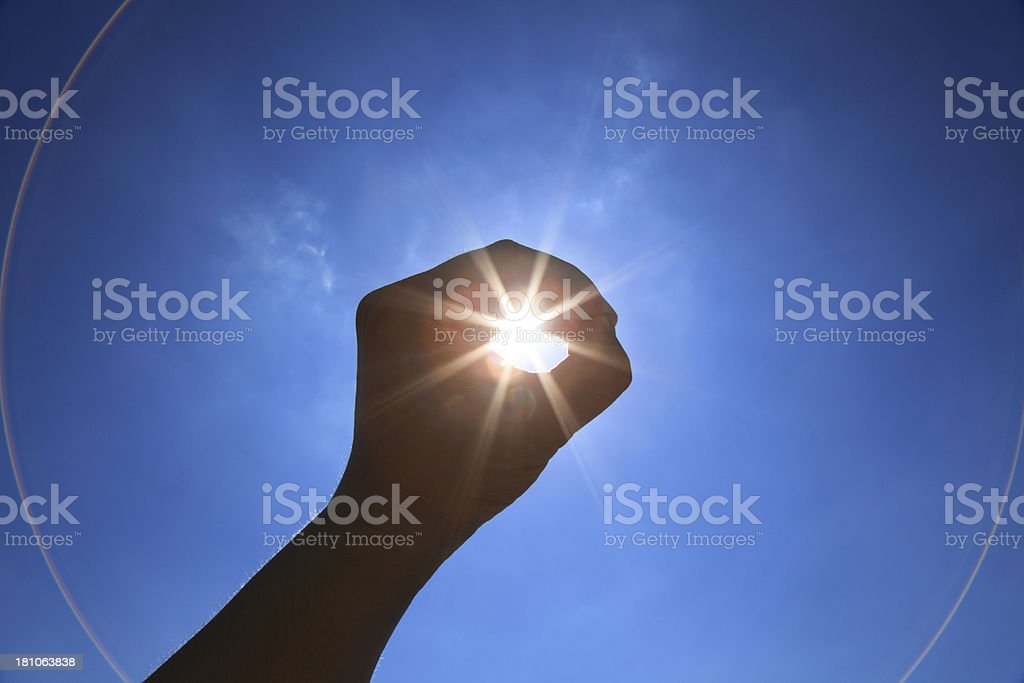 Hand raised towards sky encircling sun stock photo
