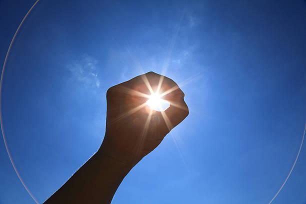 hand heben in richtung himmel einer umlaufenden sonne - solarleuchten stock-fotos und bilder