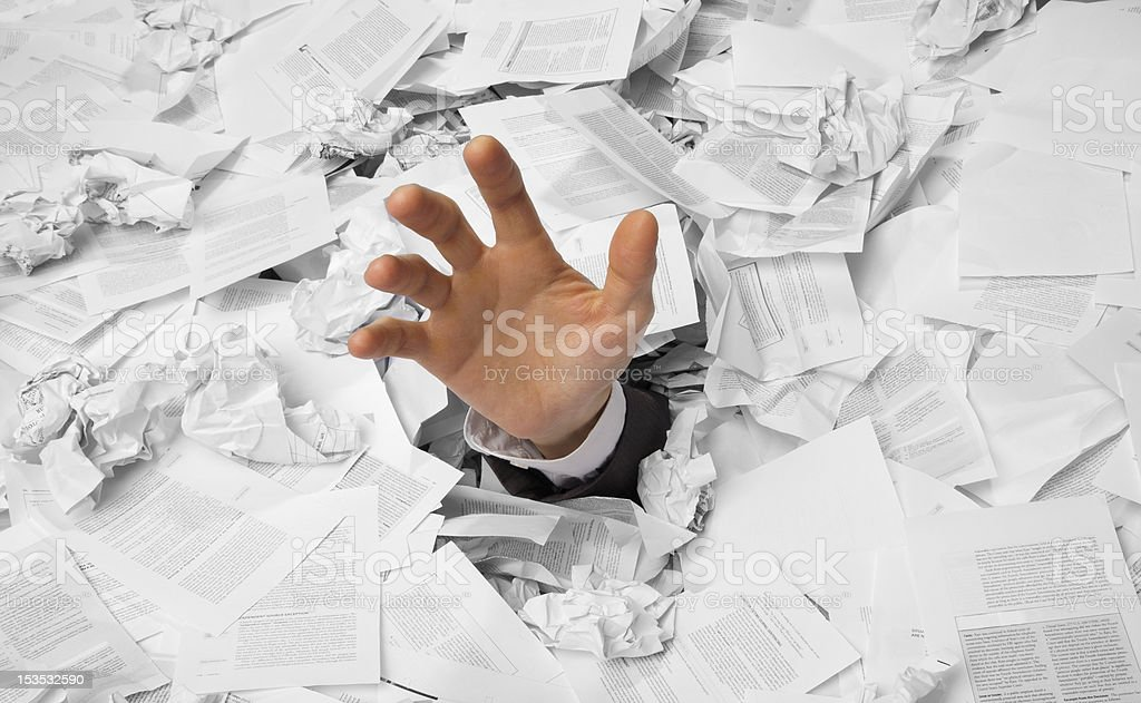 Hand reaches out from crumpled papers stock photo