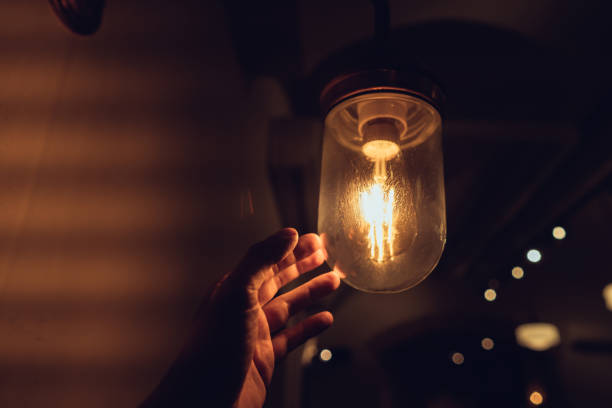 Hand reaching for a vintage light bulb. stock photo