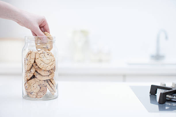 Hand reaching for cookie in jar  temptation stock pictures, royalty-free photos & images