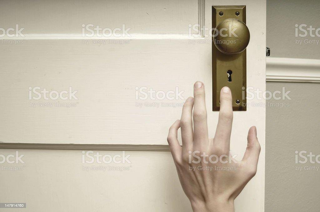 Hand reaching for doorknob stock photo