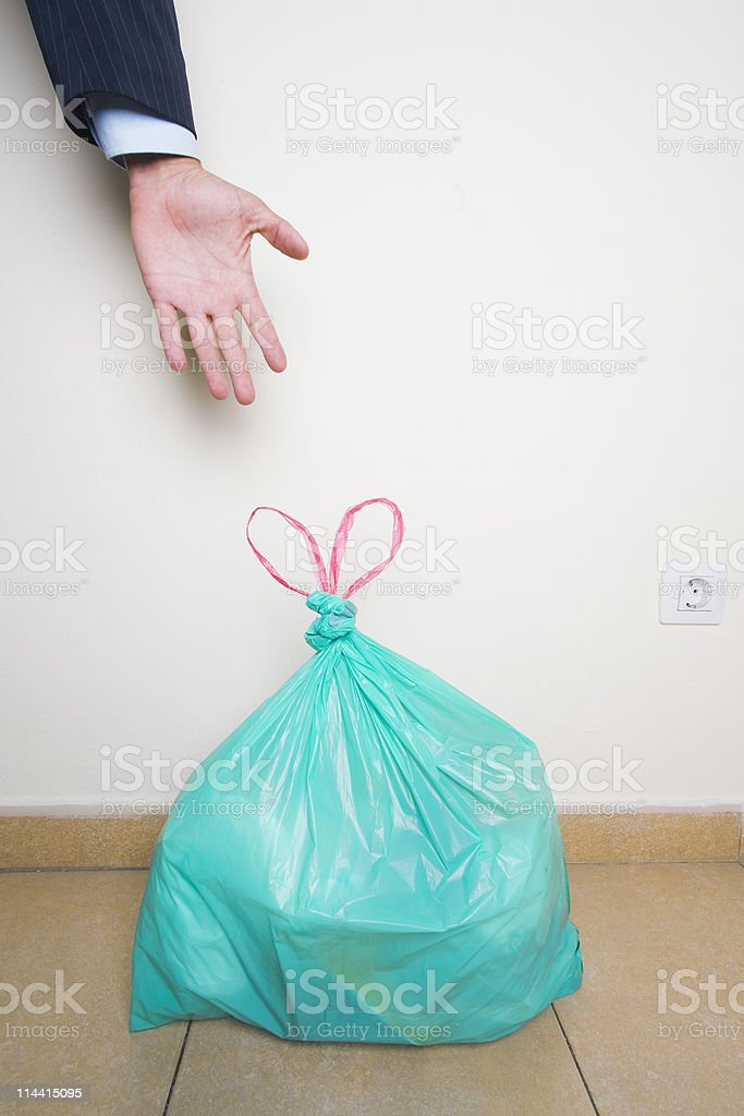 Hand reaching for green plastic bag royalty-free stock photo