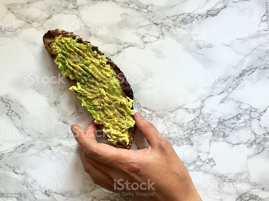 Hand reaching for homemade avocado toast on marble kitchen countertop stock photo