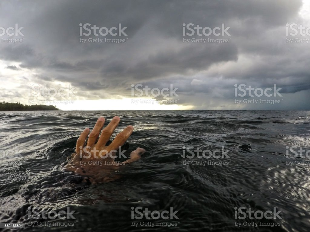 Hand reaching for horizon in the ocean stock photo