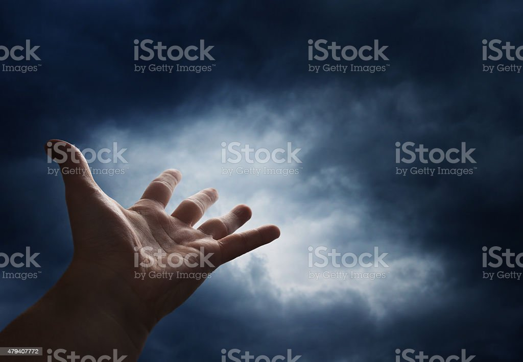 Hand reaching for the cloud in the sky stock photo