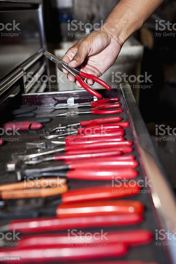 Hand reaching in toolbox for wrench stock photo