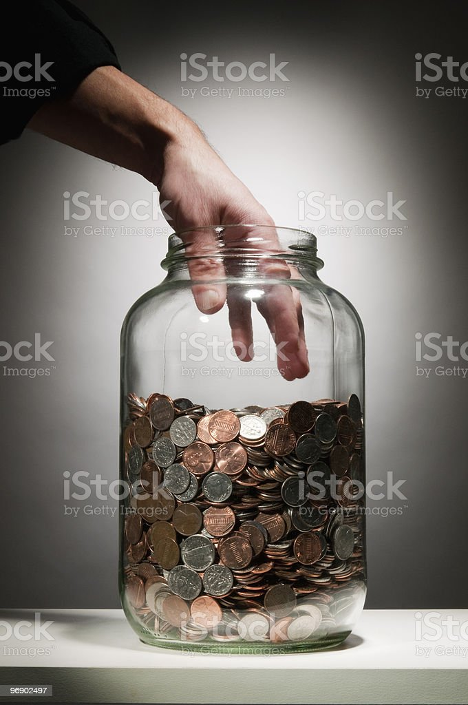 Hand reaching into jar of coins royalty-free stock photo