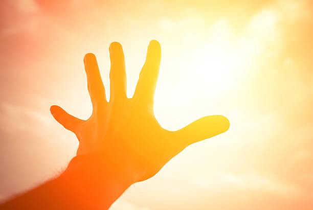 Hand reaching to sunshine sky. stock photo