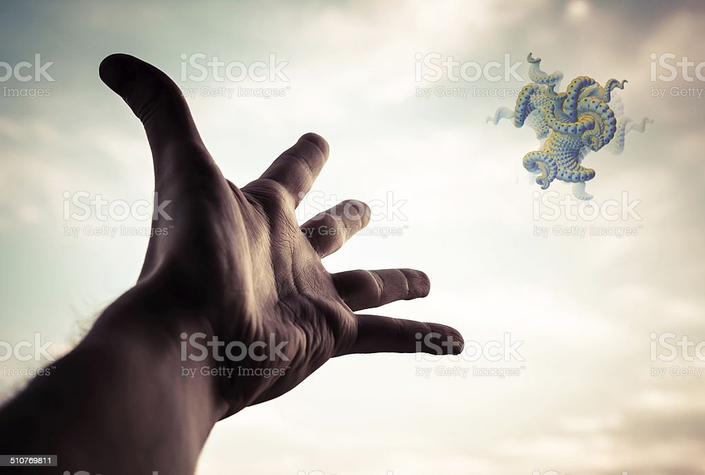 Hand of a man reaching to the fractal figure in sky. Conceptual...