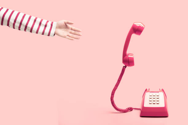 hand reaching to the pink retro telephone, phone calling on pink background, handset floating on pink background. concept of sale or deal - squillare foto e immagini stock